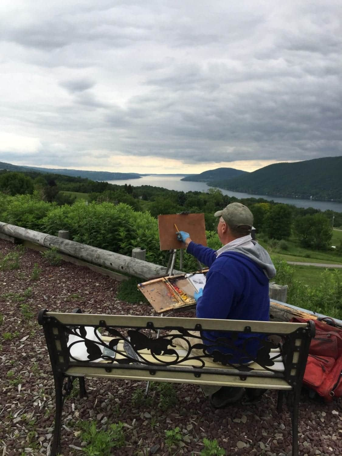 An artist painting plein air... sitting on a bench overlooking Canandaigua Lake on a moody day. This is part of the Plein Air Festival held annually in Canandaigua, Ontario County, NY