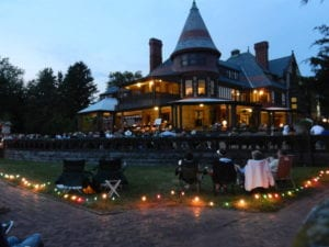 Moonlight Stroll at Sonnenberg Gardens and Mansion, located in Canandaigua, with people sitting in chairs outside the lit-up mansion listening to music... just ten minutes from the 1795 Acorn Inn B & B.