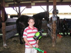 boy holding rose in front of horse