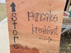 sign pointing to store and to pancake breakfast