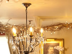 The Gathering Room at the 1795 Acorn Inn has a chandelier as it's center. Along two rods that run across the ceiling, grapevine is entwine with small white lights to create a romantic atmostphere.