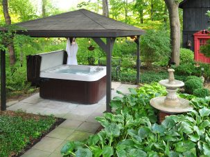 jacuzzi tub and fountain surrounded by shrubbery