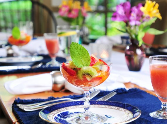 Fruit in parfait glasses on table set for breakfast with juice and water