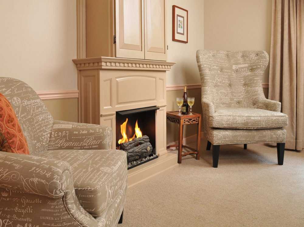 Angell Room with blazing fireplace and 2 chairs
