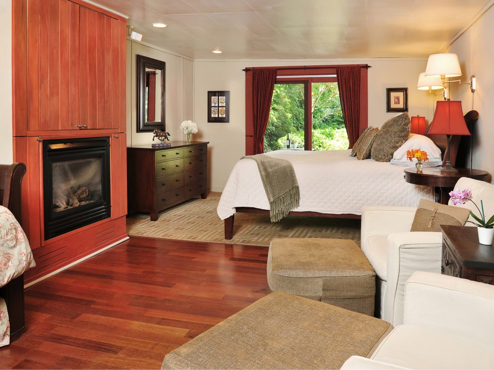 Barn Suite bedroom with bed, blazing fireplace, chairs for relaxing