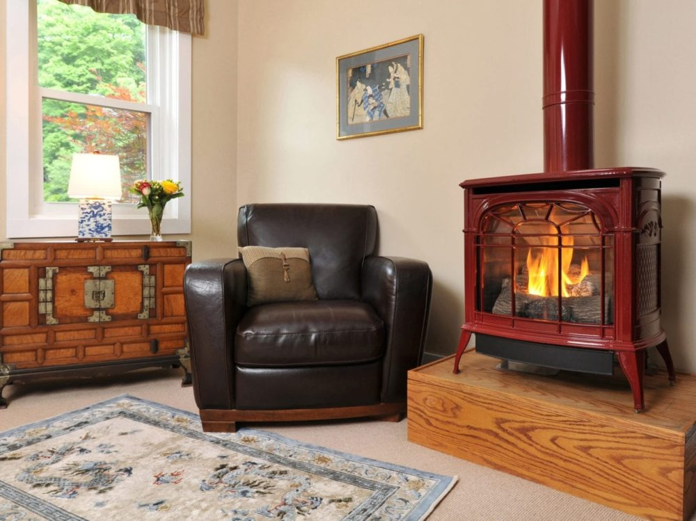Fireplace with blazing fire, chair for relaxing, dresser, in Bristol Suite