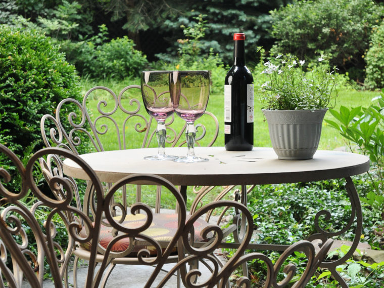 bottle of line and two glasses on table in yard