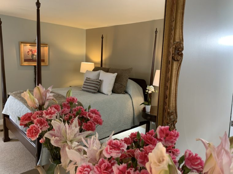 Hotchkiss Room showing bed through mirror with pink flowers in front