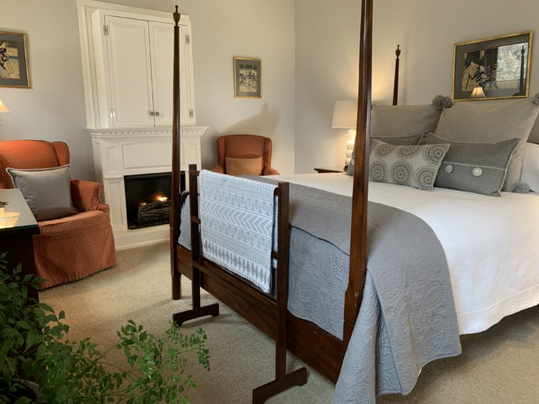 Wilder Room with 4-poster bed, quilt rack, gray pillows, coral chairs