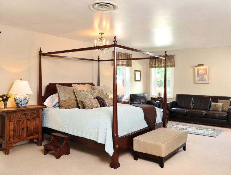 4-poster bed with white linens and sofa in Bristol Suite