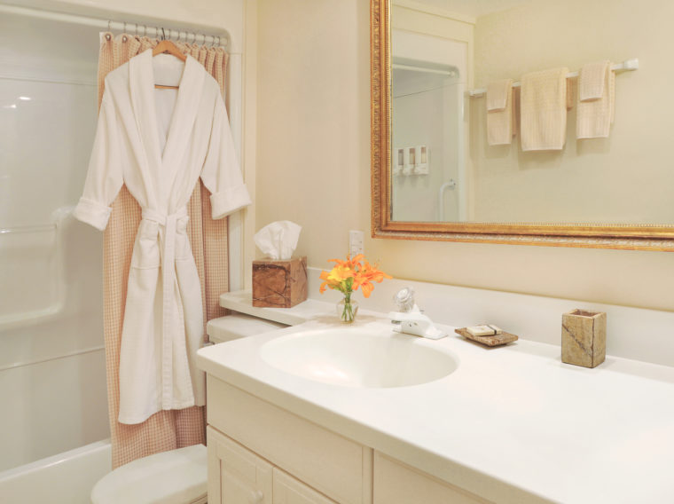 bathroom with white robe hanging on shower