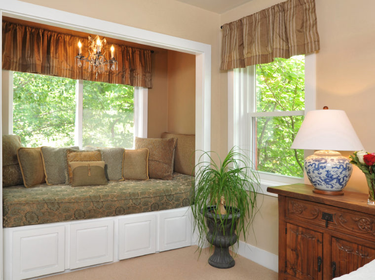 window seat and dresser with lamp and flowers in Bristol Suite
