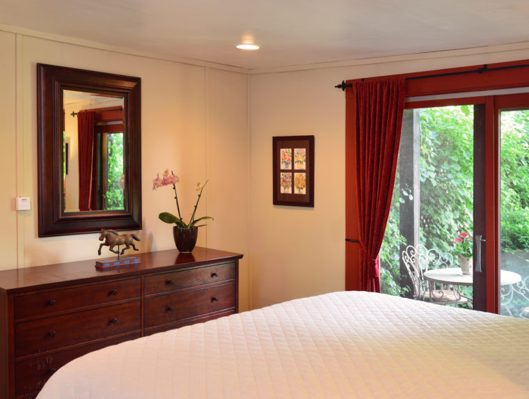 Barn Suite bedroom with dresser and mirror and bed with white bedspread