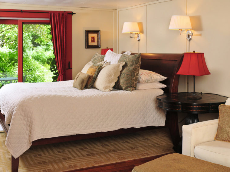 Bed with white bedspread and lots of pillows in Barn Suite