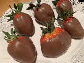 chocolate-covered strawberries on white doiley