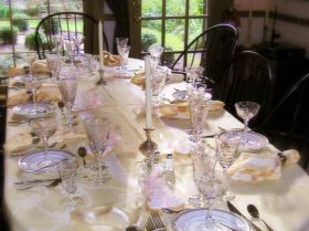 dining room table set with plates and crystal