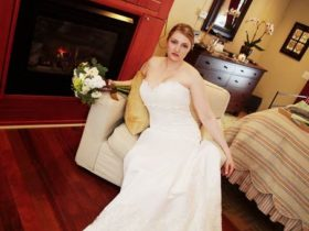 bride holding bouquet sitting in chair in front of fireplace