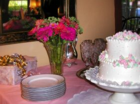 decorated wedding cake and pink flowers with gifts ready for the serving