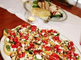 wedding hors d'oeuvres... bruscetta, toast with basil, mozzarella and tomato with a balsamic glaze, apples, crackers and brie in the background with bridge's wedding bouquet