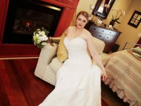 bride in a white strapless wedding gown holding bouquet sitting in chair in front of fireplace in the Barn Suite of the 1795 Acorn Inn Bed and Breakfast... perfect for honeymooners