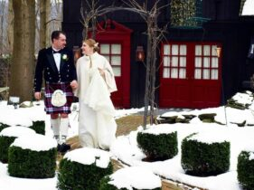 Bride in a white lace wedding gown and cape and groom in a traditional kilt looking at each other lovingly while walking from the Barn Suite to the Gathering Room at the 1795 Acorn Inn Bed and Breakfast on a winter's day with snow covered grounds