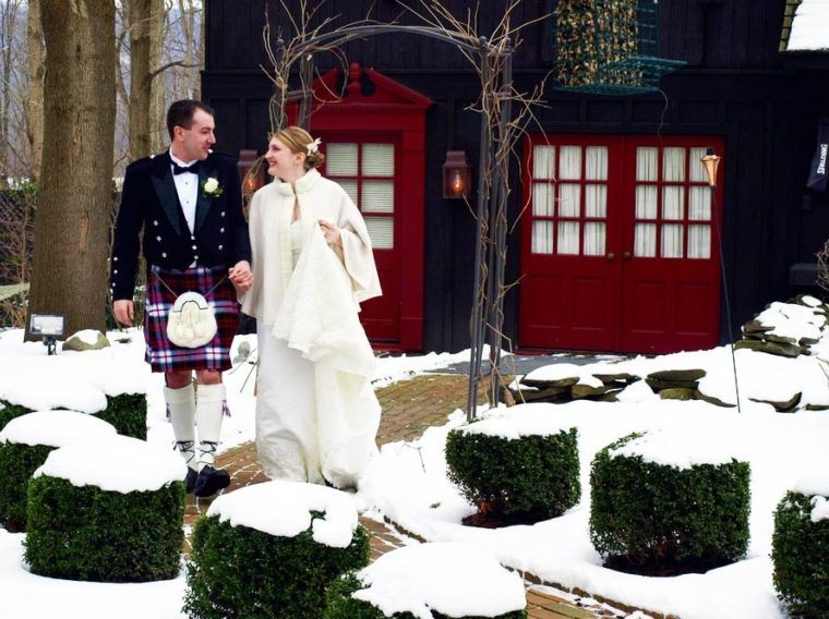 groom in kilt and bride with snow on ground