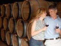 Couple dressed in summer clothing tasting red wine with wine barrels in the backgroud.