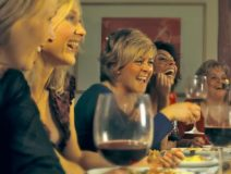 laughing women tasting wine