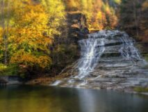 Buttermilk Falls gently flowing down steps of rock during fall foliage with yellow trees and still pond below