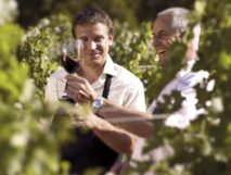 Two men tasting red wine in vineyard. The Finger Lakes have quickly become a notable wine region in the U.S.