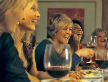 laughing women tasting wine