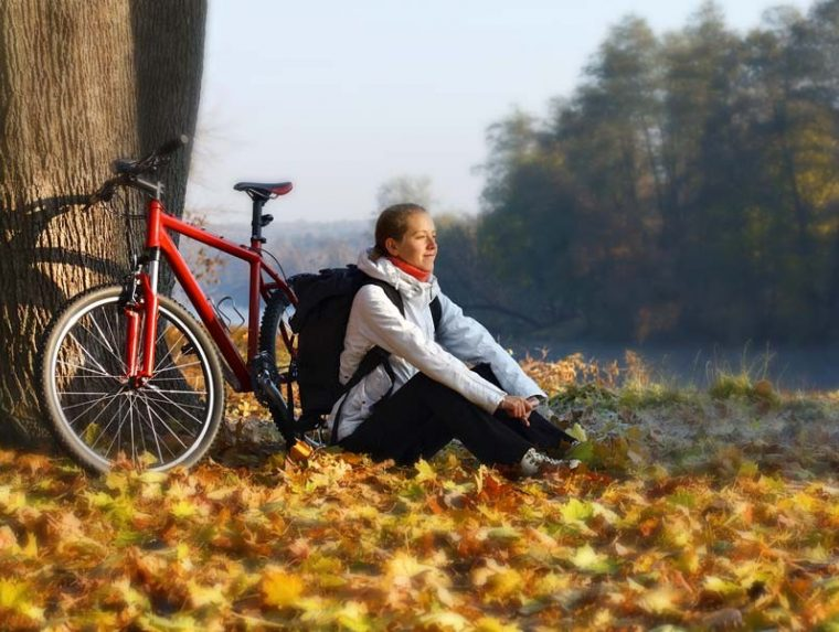 lady sitting on leaves on ground leaning against bike